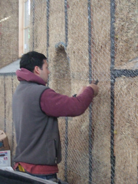 Wiring chicken wire to the face of the bales